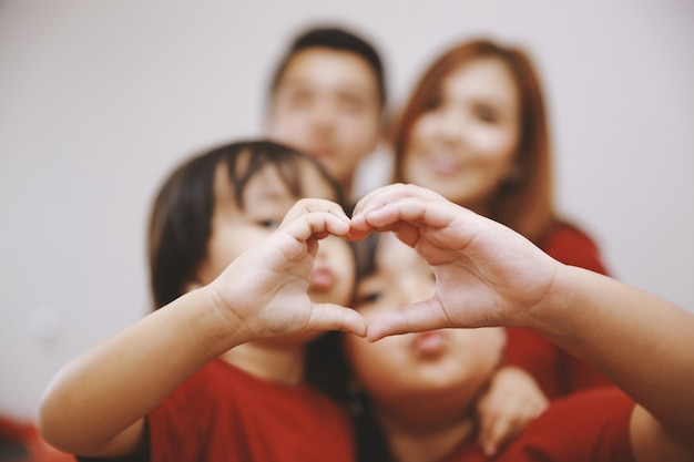 Close up of two little daughters making heart shape with hands with blurry photo of parent on the background love and happy family concept