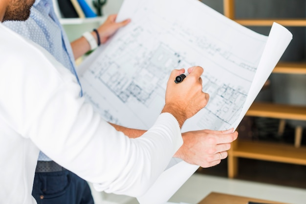 Close-up of two male architect analyzing blueprint