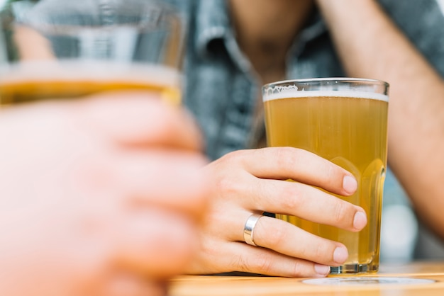 Close-up of two male's hand holding glass of beer