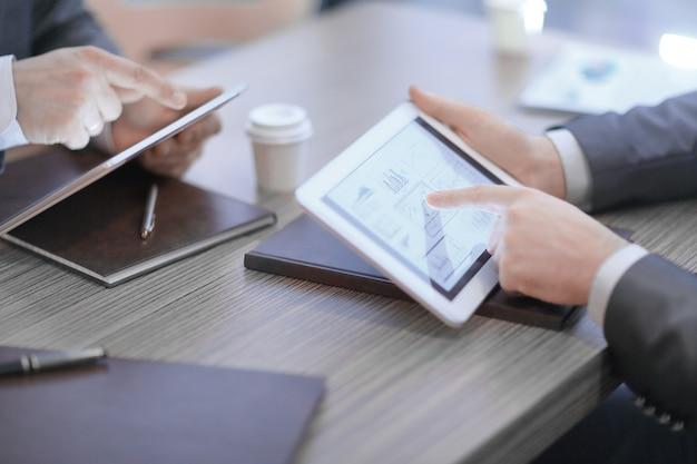 Close up.two 회원은 디지털 태블릿을 사용하여 재정적 인 oches를 구성합니다.