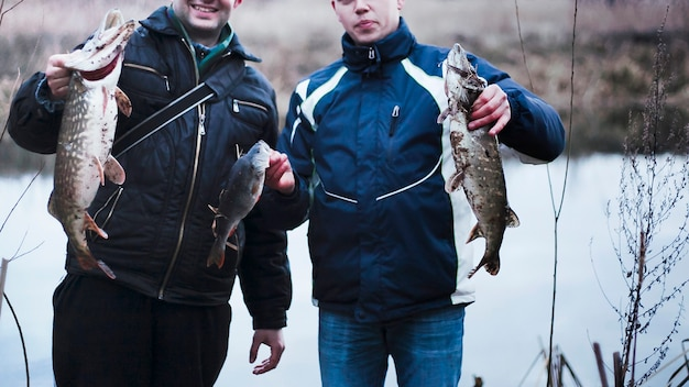Close-up of two men holding caught fish