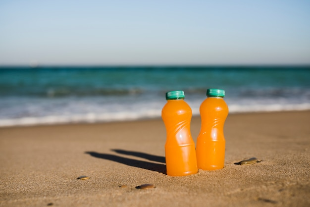 Close-up of two orange juice bottles near the seashore