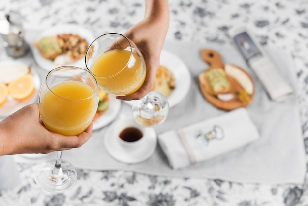Close-up of a two people toasting juice glasses over the breakfast on table