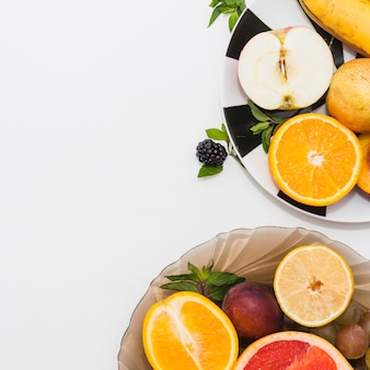 Close-up of two plates with fresh halved fruits on white background