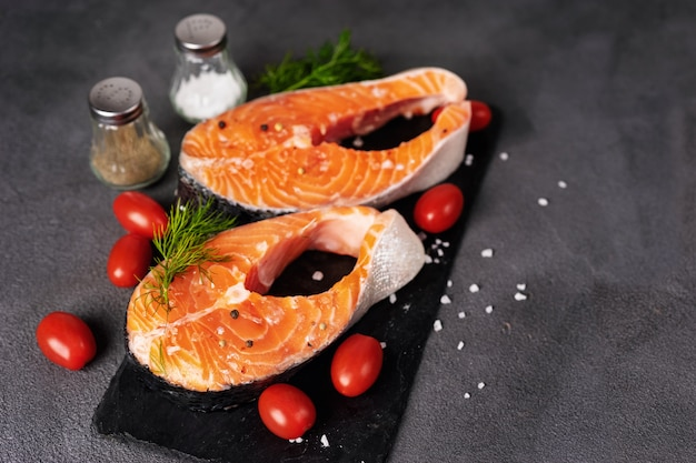 Close up of two raw salmon steaks on dark background