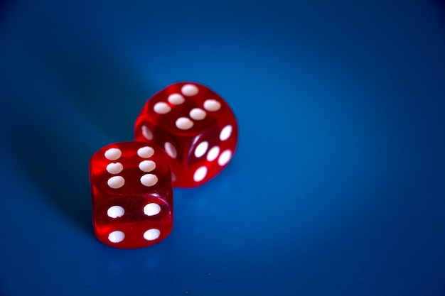 Close-up of two red dices with sixes on the top on a blue background