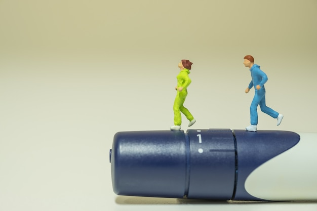 Close up of  two runner miniature figures running on lancet for check blood sugar level