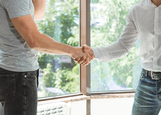 Close up of two shaking male hands casual wear.
