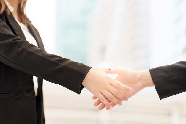 Close up of two smile businesswoman shaking hands on blurred building background.