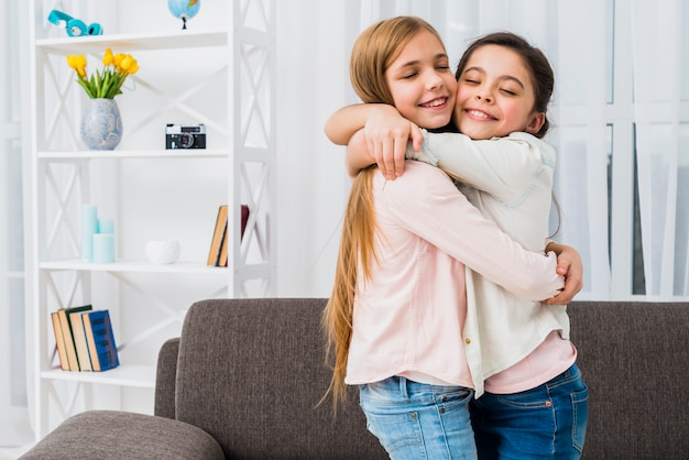 Close-up of two smiling girls hugging each other at home