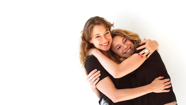 Close-up of two smiling sisters hugging each other on white background