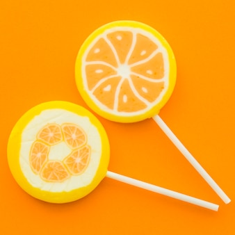 Close-up of two sweet lollipops on orange backdrop