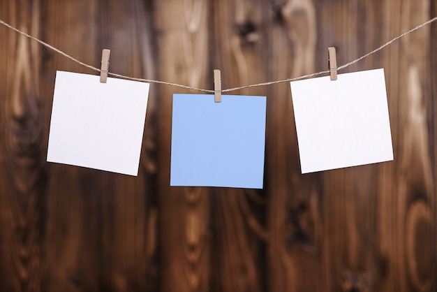 Close up of two white and one blue note papers hung by wooden clothes pegs on a brown wooden background