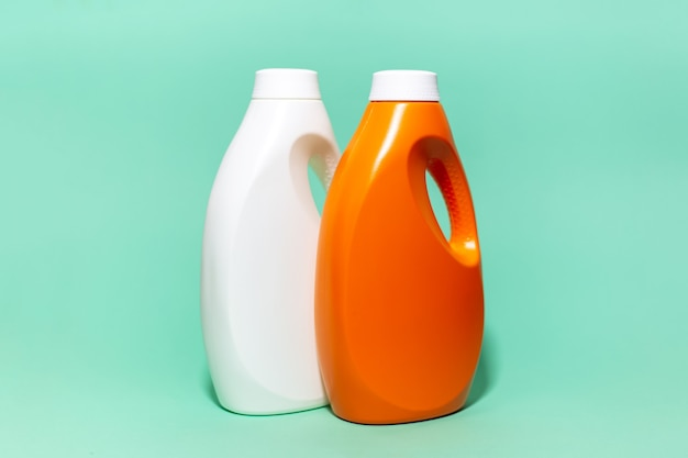 Close-up of two, white and orange, detergent bottles on wall of aqua menthe color.
