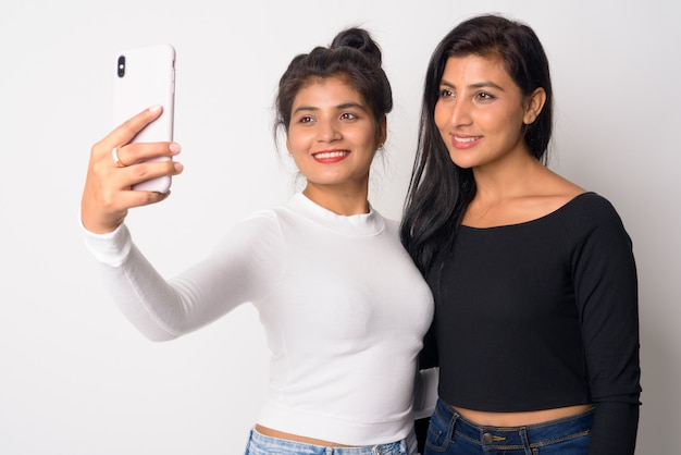 Close up of two young beautiful persian women together as sisters isolated