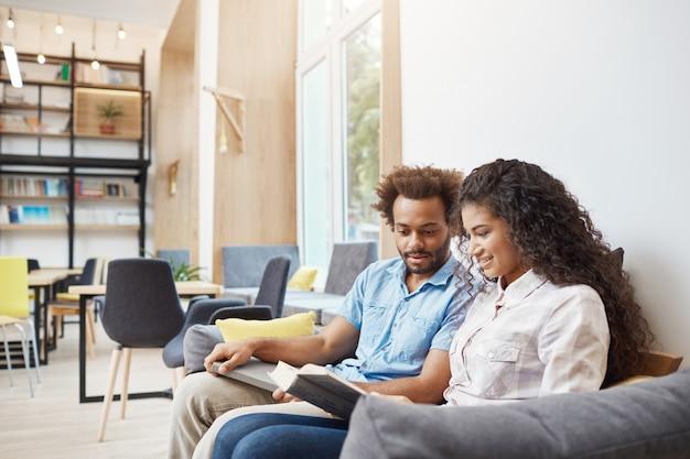 Primo piano di due giovani studenti multietnici seri seduti sul divano nella biblioteca universitaria guardando attraverso le informazioni per gli esami nei libri, parlando della vita universitaria