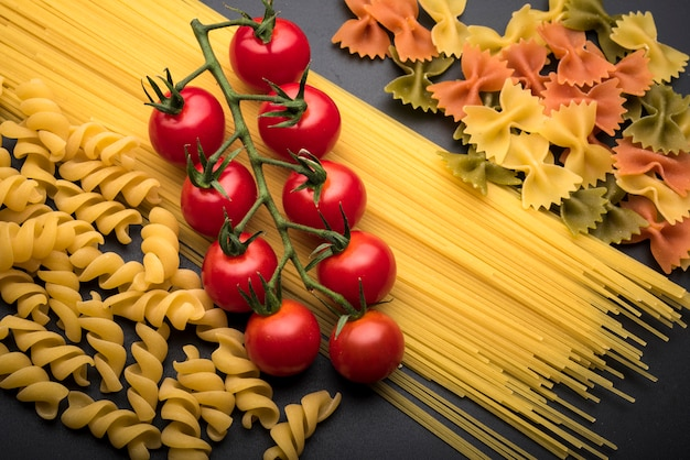 Close-up of types of uncooked pasta and fresh juicy red tomatoes