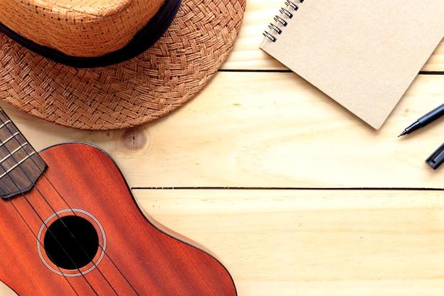 Close-up ukulele and hat on wood background. over light