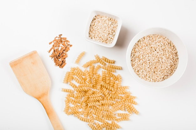 Close-up of uncooked fusilli pasta; rice and crushed cinnamon with spatula on white background