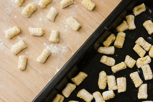 Close-up of uncooked homemade potato gnocchi pasta on baking tray and desk