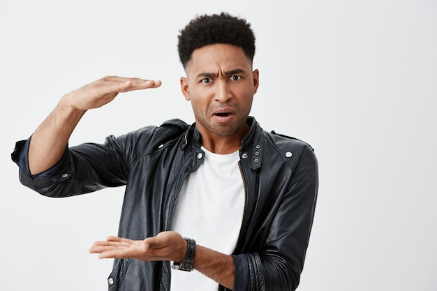 Close up of unhappy mature black-skinned african male student with curly hair in white casual t-shirt and black leather jacket showing big size with hands looking in camera with angry expression.