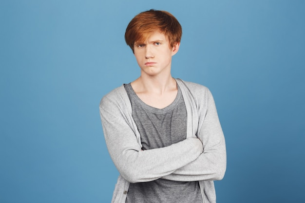 Close up of unhappy young good-looking ginger boy in casual stylish outfit crossing hands,  with offended and unsatisfied face expression, after argument with girlfriend.