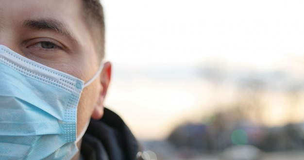 Close up of unhealthy guy wearing protection from coronavirus in city. pandemic concept. infected person.