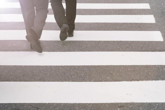 Close-up on unidentified people legs crossing street