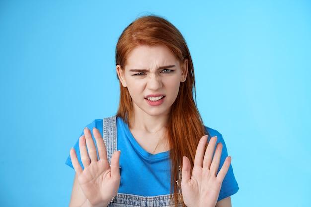 クローズアップ無関心な不機嫌な無知な赤毛のガールフレンド、しかめっ面はうんざりしたしかめっ面を上げる手をブロック停止ジェスチャー、拒否、腕を振って拒否の兆候なし、青い背景に立つ