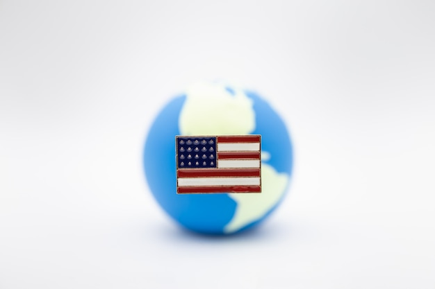 Close up of united state of america pin national flag over mini world ball on white