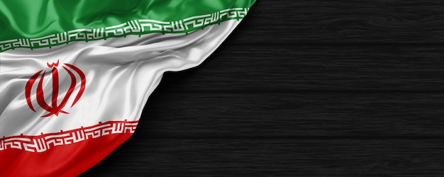 Close up of united states of iran flag on the black wooden background 3d render