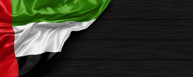 Close up of united states of united arab emirates flag on the black wooden background 3d render