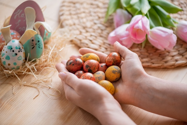 Close-up of unknown woman holding handful of small easter eggs above wooden table with flowers and decorative eggs