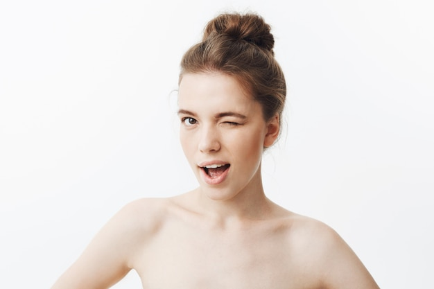 Close up of unny young girl with brown long hair in bun hairstyle and skinny body type, being half naked, holding hands on waist, winking, smiling with flirty expression.