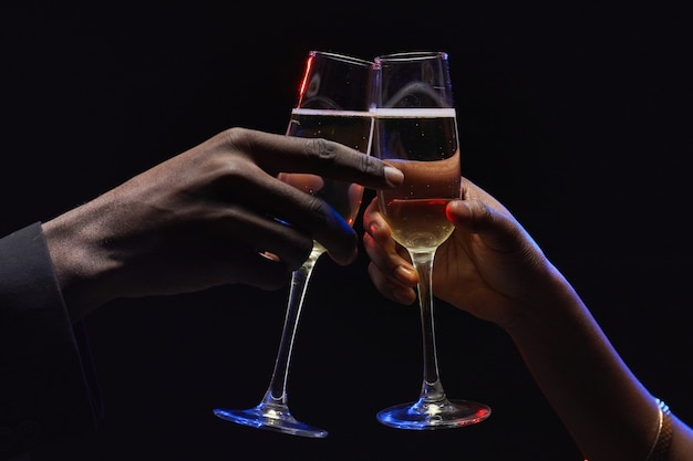 Close up of unrecognizable african-american couple clinking champagne glasses in dark, copy space