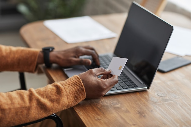 Close up of unrecognizable african-american man holding mockup credit card while online shopping via laptop, copy space