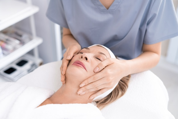 Close-up of unrecognizable beauty professional giving facial massage to relaxed mature woman in beauty salon