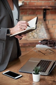 Close-up of unrecognizable businesswoman in jacket standing at desk and writing down ideas in diary