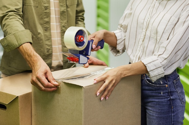 Close up of unrecognizable couple packing boxes with tape gun while standing in self storage unit, copy space