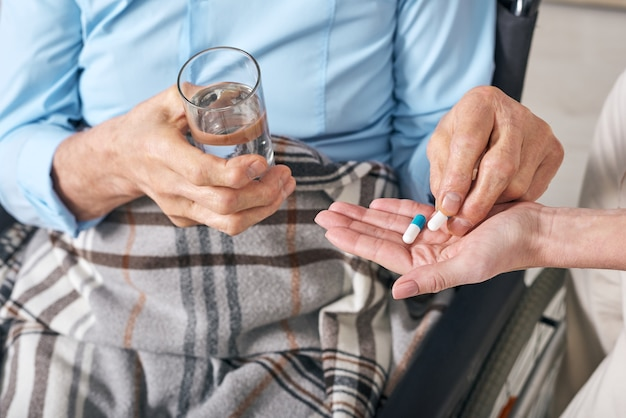 Close-up of unrecognizable elderly man sitting under blanket in wheelchair and taking pills given by nurse