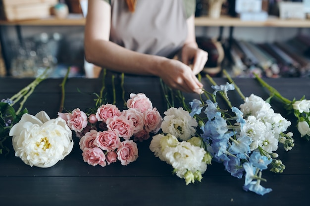 Close-up of unrecognizable florist standing at dark blue wooden table and preparing flower for arranging bouquet