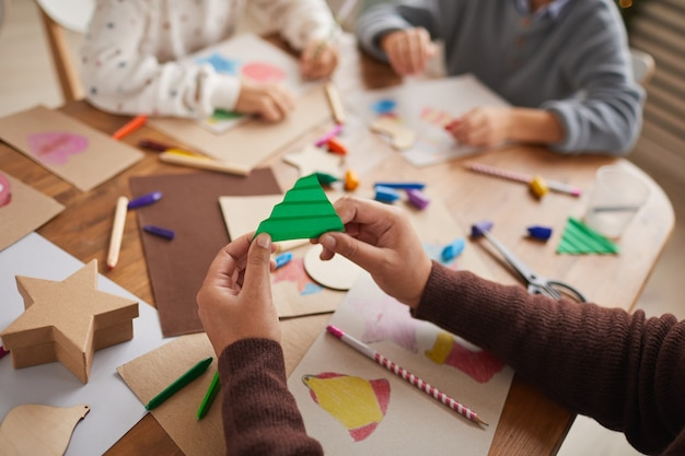 Close up of unrecognizable girl holding paper christmas tree while doing art and craft project with group of children, copy space