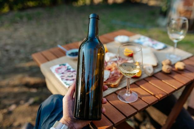 ワインのボトルを持っているクローズアップの認識できない手。前菜とおいしい料理をセットしたテーブルワインの試飲とピクニックのコンセプト。