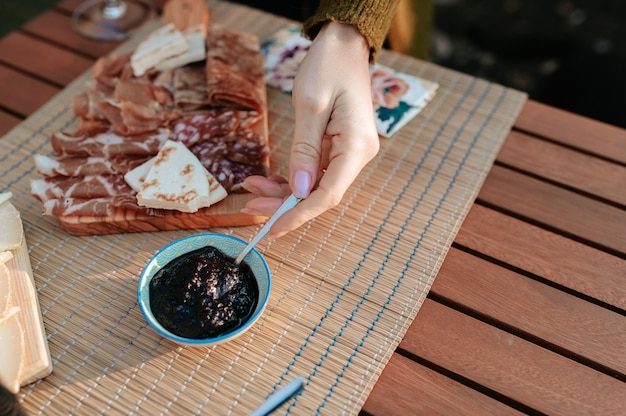 Крупный план до неузнаваемости рукой, подающей варенье. столовый сервиз с закусками и вкусной едой. концепция пикника.