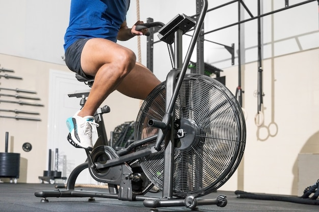 Close up of an unrecognizable man doing cardio training on stationary air bike machine with fan at t...
