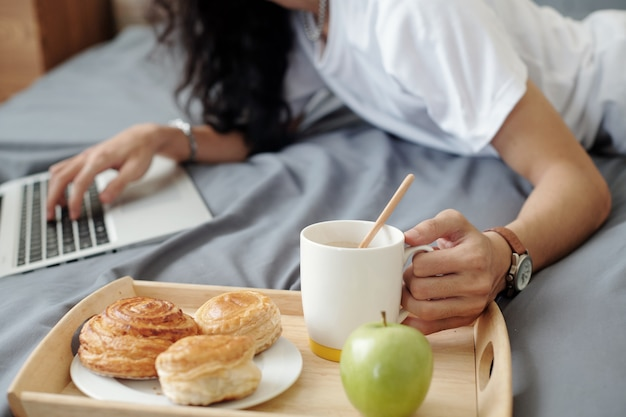 Close-up of unrecognizable man lying on bed and using laptop, he having breakfast in bed while working at home