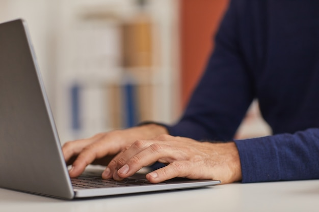 Close up of unrecognizable mature man using laptop while working at home office, focus on male hands typing on keyboard, copy space
