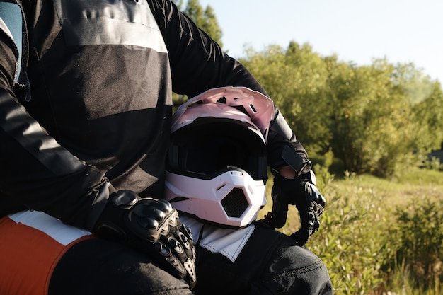 Close-up of unrecognizable motorcyclist in protective gloves sitting with helmet in forest