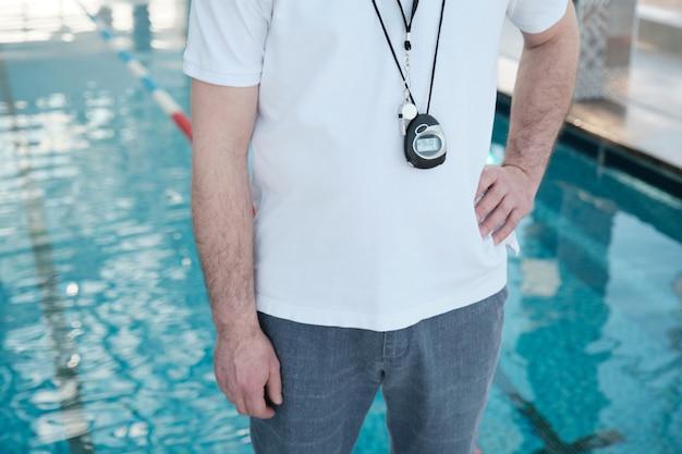 클로즈업 인식 할 수없는 수영 코치와 스톱워치 및 엉덩이에 손으로 서있는 가슴에 휘파람