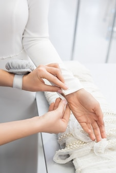 Close-up of unrecognizable tailor with pincushion on wrist buttoning wedding dress sleeve at gown fitting